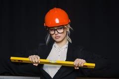 Schöne blonde Geschäftsfrau mit Anwendungsreihe im Dachbodenbüro im orange Bausturzhelm und -klage Stockfoto