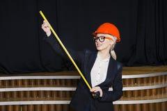 Schöne blonde Geschäftsfrau mit Anwendungsreihe im Dachbodenbüro im orange Bausturzhelm und -klage Stockfotos
