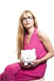 Schöne blonde Geschäftsfrau mit den Brillen, die piggy Ba halten Lizenzfreies Stockfoto