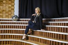 Schöne blonde Geschäftsfrau mit den geschwollenen Lippen im Dachbodenbüro in der Klage Die goldene Taste oder Erreichen für den H Stockbild