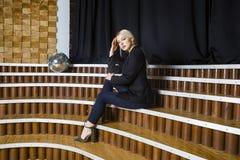 Schöne blonde Geschäftsfrau mit den geschwollenen Lippen im Dachbodenbüro in der Klage Die goldene Taste oder Erreichen für den H Lizenzfreie Stockfotografie