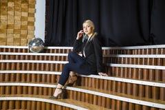 Schöne blonde Geschäftsfrau mit den geschwollenen Lippen im Dachbodenbüro in der Klage Die goldene Taste oder Erreichen für den H Stockfotografie