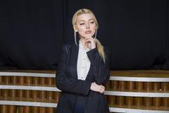 Schöne blonde Geschäftsfrau mit den geschwollenen Lippen im Dachbodenbüro in der Klage Die goldene Taste oder Erreichen für den H Lizenzfreies Stockfoto