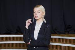 Schöne blonde Geschäftsfrau mit den geschwollenen Lippen im Dachbodenbüro in der Klage Die goldene Taste oder Erreichen für den H Lizenzfreies Stockbild