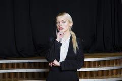 Schöne blonde Geschäftsfrau mit den geschwollenen Lippen im Dachbodenbüro in der Klage Die goldene Taste oder Erreichen für den H Stockfoto