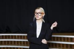 Schöne blonde Geschäftsfrau mit den geschwollenen Lippen im Dachbodenbüro in den orange Gläsern und in der Klage Die goldene Tast Stockfotografie