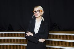 Schöne blonde Geschäftsfrau mit den geschwollenen Lippen im Dachbodenbüro in den orange Gläsern und in der Klage Die goldene Tast Lizenzfreie Stockbilder