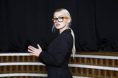 Schöne blonde Geschäftsfrau mit den geschwollenen Lippen im Dachbodenbüro in den orange Gläsern und in der Klage Die goldene Tast Stockfotos