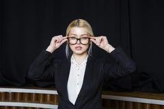 Schöne blonde Geschäftsfrau mit den geschwollenen Lippen im Dachbodenbüro in den orange Gläsern und in der Klage Die goldene Tast Lizenzfreies Stockbild