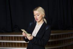 Schöne blonde Geschäftsfrau mit Geld im Dachbodenbüro im schwarzen Anzug Stockfoto