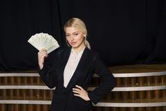 Schöne blonde Geschäftsfrau mit Geld im Dachbodenbüro im schwarzen Anzug Lizenzfreies Stockfoto