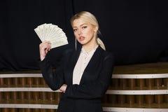 Schöne blonde Geschäftsfrau mit Geld im Dachbodenbüro im schwarzen Anzug Lizenzfreies Stockbild