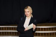Schöne blonde Geschäftsfrau mit Geld im Dachbodenbüro im schwarzen Anzug Stockfotos