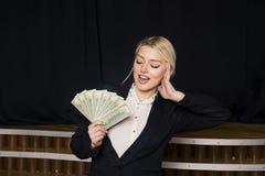 Schöne blonde Geschäftsfrau mit Geld im Dachbodenbüro im schwarzen Anzug Stockbilder