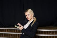 Schöne blonde Geschäftsfrau mit Geld im Dachbodenbüro im schwarzen Anzug Lizenzfreie Stockfotografie