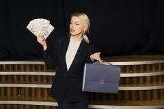 Schöne blonde Geschäftsfrau mit Geld im Dachbodenbüro im schwarzen Anzug Stockfotografie
