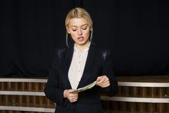 Schöne blonde Geschäftsfrau mit Geld im Dachbodenbüro im schwarzen Anzug Stockbild