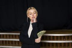 Schöne blonde Geschäftsfrau mit Geld im Dachbodenbüro im schwarzen Anzug Lizenzfreie Stockbilder