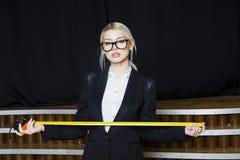 Schöne blonde Geschäftsfrau mit Maßband im Dachbodenbüro in den orange Gläsern und im schwarzen Anzug Die goldene Taste oder Erre Stockfoto