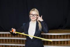 Schöne blonde Geschäftsfrau mit Maßband im Dachbodenbüro in den orange Gläsern und im schwarzen Anzug Die goldene Taste oder Erre Lizenzfreie Stockfotos