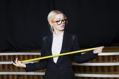 Schöne blonde Geschäftsfrau mit Maßband im Dachbodenbüro in den orange Gläsern und im schwarzen Anzug Die goldene Taste oder Erre Stockfotografie