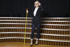 Schöne blonde Geschäftsfrau mit Maßband im Dachbodenbüro in den orange Gläsern und im schwarzen Anzug Die goldene Taste oder Erre Stockbilder