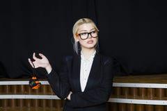 Schöne blonde Geschäftsfrau mit Maßband im Dachbodenbüro in den orange Gläsern und im schwarzen Anzug Die goldene Taste oder Erre Lizenzfreies Stockbild
