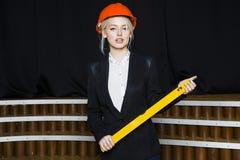 Schöne blonde Geschäftsfrau mit Maßband im Dachbodenbüro in den orange Gläsern und im schwarzen Anzug Die goldene Taste oder Erre Stockbild
