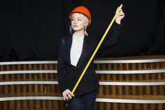 Schöne blonde Geschäftsfrau mit Maßband im Dachbodenbüro im orange Bausturzhelm und -klage Stockfotografie