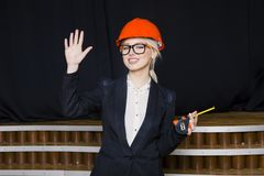 Schöne blonde Geschäftsfrau mit Maßband im Dachbodenbüro im orange Bausturzhelm und -klage Stockbilder