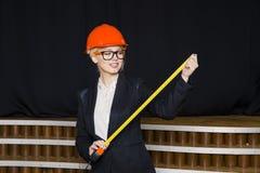Schöne blonde Geschäftsfrau mit Maßband im Dachbodenbüro im orange Bausturzhelm und -klage Stockfotos