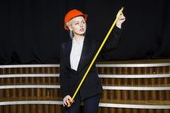 Schöne blonde Geschäftsfrau mit Maßband im Dachbodenbüro im orange Bausturzhelm und -klage Lizenzfreie Stockfotos