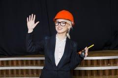 Schöne blonde Geschäftsfrau mit Maßband im Dachbodenbüro im orange Bausturzhelm und -klage Lizenzfreie Stockfotografie