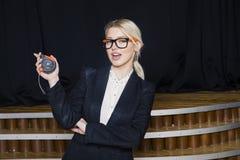 Schöne blonde Geschäftsfrau mit Maßband im Dachbodenbüro im orange Bausturzhelm und -klage Lizenzfreies Stockbild