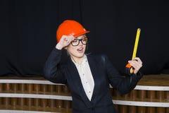 Schöne blonde Geschäftsfrau mit Maßband im Dachbodenbüro im orange Bausturzhelm und -klage Stockfoto