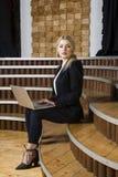 Schöne blonde Geschäftsfrau mit Notizbuch und Laptop am Dachbodenbüro an der herein und Klage Stockbild