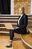 Schöne blonde Geschäftsfrau mit Notizbuch und Laptop am Dachbodenbüro an der herein und Klage Stockbilder