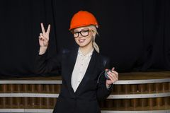 Schöne blonde Geschäftsfrau mit Notizbuch und Laptop im Dachbodenbüro im orange Bausturzhelm und -klage Lizenzfreies Stockbild