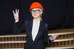 Schöne blonde Geschäftsfrau mit Notizbuch und Laptop im Dachbodenbüro im orange Bausturzhelm und -klage Stockfotos
