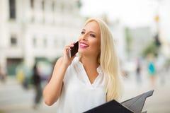Schöne blonde Geschäftsfrau am Telefon im Freien Stockfotografie