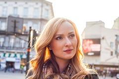 Schöne blonde glückliche Frau, die auf die Straße in der Stadt geht Lizenzfreie Stockbilder
