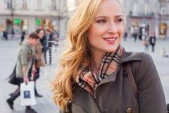 Schöne blonde glückliche Frau, die auf die Straße in der Stadt geht Outd Lizenzfreies Stockbild