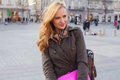 Schöne blonde glückliche Frau, die auf die Straße in der Stadt geht Outd Lizenzfreie Stockbilder