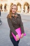 Schöne blonde glückliche Frau, die auf die Straße in der Stadt geht Outd Stockbilder