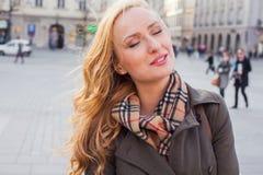 Schöne blonde glückliche Frau, die auf die Straße in der Stadt geht Outd Stockfotografie