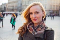 Schöne blonde glückliche Frau, die auf die Straße in der Stadt geht Outd Stockbild