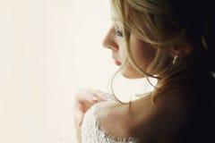 Schöne blonde Hochzeitsbraut im Make-up und Schleier in einem weißen Dr. Stockfotografie