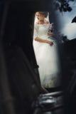 Schöne blonde Hochzeitsbraut im weißen Kleid, das in elega kommt Lizenzfreies Stockbild