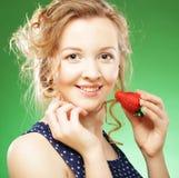 Schöne blonde Holding eine Erdbeere Lizenzfreie Stockbilder