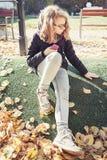 Schöne blonde Jugendliche in den Gläsern, die im Park sitzen Lizenzfreie Stockbilder
